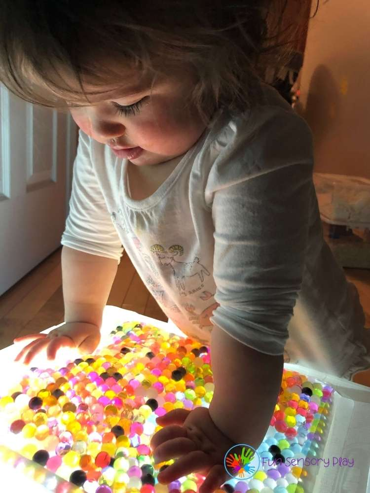 child playing with water bead light box